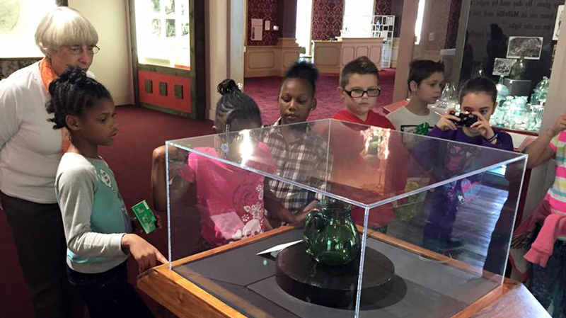 Seven students look at a handmade, green glass pitcher during a tour with the museum docent.
